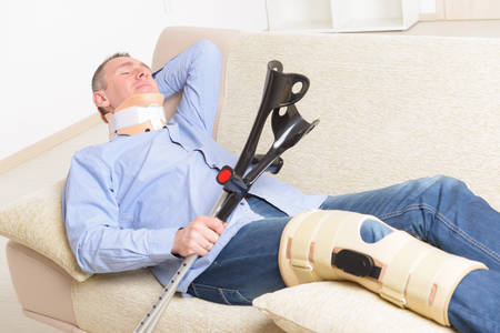 stabilization: Man with leg in neck brace, knee cages and crutches for stabilization and support resting on a sofa