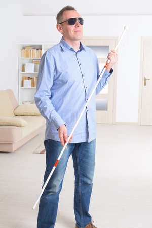 a blind: Blind man with white stick and dark glasses at home
