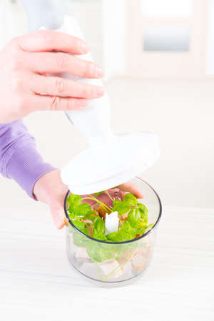 Woman using a hand blender to make a pate Stock Photo