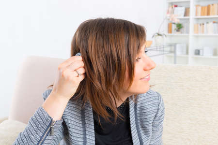 cochlear: Young, smiling woman showing cochlear implant