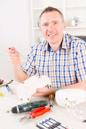can opener: Smiling man repairing electric can opener at home appliance service workshop