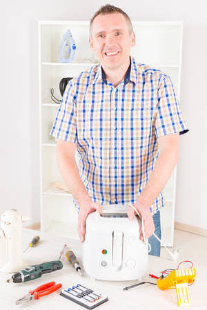 fryer: Smiling man holding repaired deep fryer at home appliance service workshop