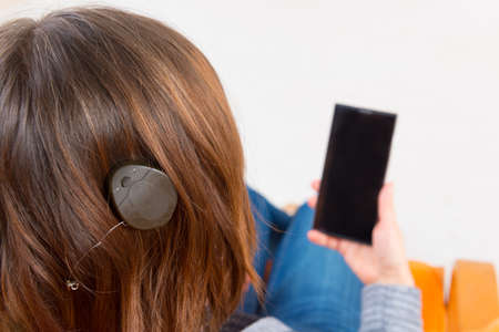 cochlear: Deaf woman with cochlear implant using smartphone