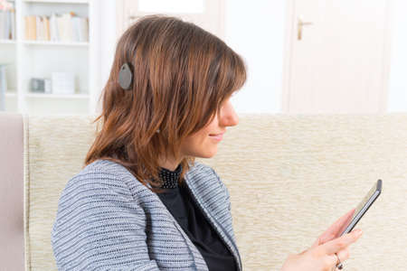 cochlear: Smiling deaf woman with cochlear implant using smartphone
