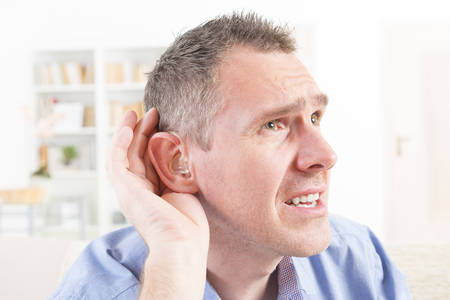 attempting: Man wearing deaf aid in ear attempting to hear something Stock Photo