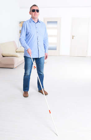 Blind man with white stick and dark glasses at home