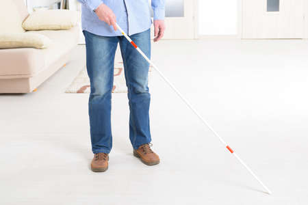 blind man: Blind man with white stick at home
