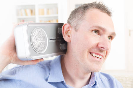 impaired: Hearing impaired man trying to listen radio at home