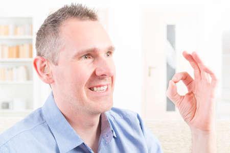 sign language: Smiling deaf man using sign language and showing OK sign