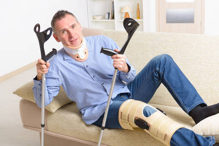 therapy equipment: Man with leg in neck brace, knee cages and crutches for stabilization and getting up for rehabilitation