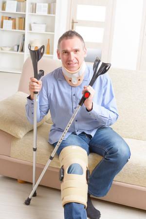 levantandose: El hombre con la pierna en cuello ortop�dico, jaulas de rodilla y muletas para la estabilizaci�n y levantarse para la rehabilitaci�n Foto de archivo