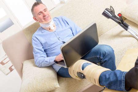 trabajando en casa: El hombre con la pierna en cuello ortop�dico, jaulas de rodilla y muletas para la estabilizaci�n y el apoyo que descansa en un sof� con el port�til.