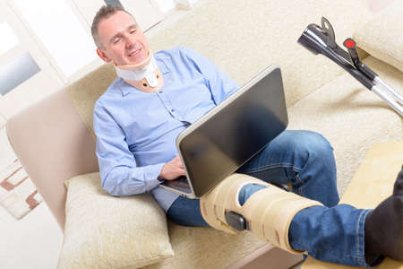 stabilization: Man with leg in neck brace, knee cages and crutches for stabilization and support resting on a sofa with laptop.