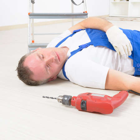 injure: Man worker laying on a floor, concept of accident at work