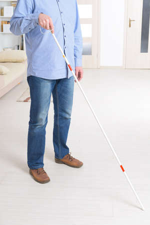 sightless: Blind man with white stick and dark glasses at home