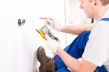 electricista: Electricista tensión toma de cheques con multímetro digital Foto de archivo