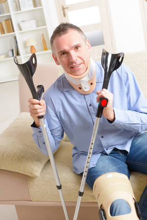stabilization: Man with leg in neck brace, knee cages and crutches for stabilization and getting up for rehabilitation