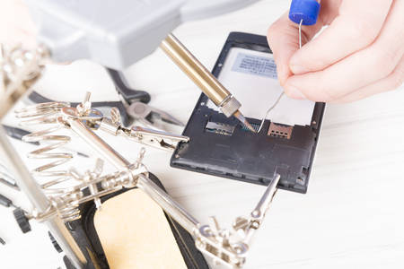 serviceman: Serviceman repairing mobile phone in the electronic workshop Stock Photo