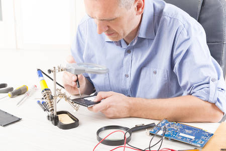 Serviceman repairing mobile phone in the electronic workshop Stock Photo