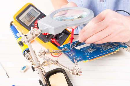 pcb: Serviceman checks PCB with a digital multimeter in the service workshop