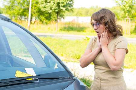 warden: Suprised woman looking on parking ticket placed under windshield wiper Stock Photo