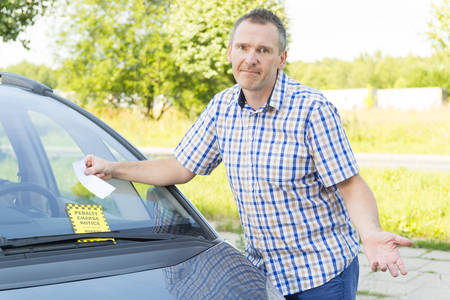unhappy man looking on parking ticket placed under windshield wiper