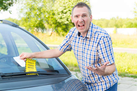 Suprised screaming man looking on parking ticket placed under windshield wiper