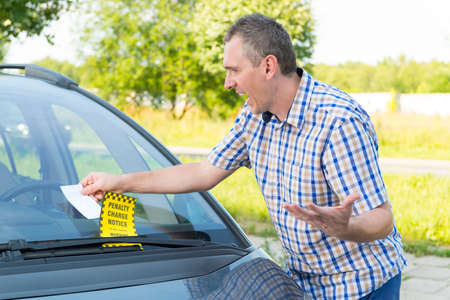 Suprised man looking on parking ticket placed under windshield wiper Stockfoto