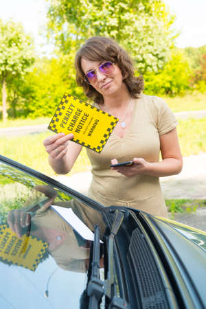 warden: Unhappy woman showing parking ticket. Focus on ticet