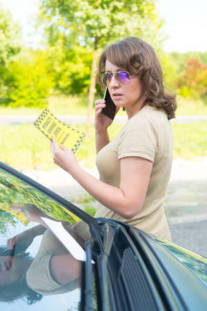parking ticket: Suprised woman looking on parking ticket placed under windshield wiper and talking on the mobile phone