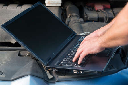 service engineer: Mobile car service engineer checking car with his laptop on the road Stock Photo