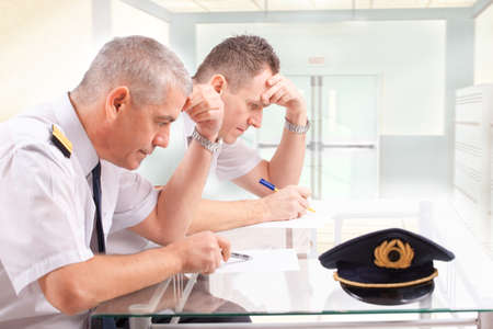 epaulets: Two airline pilots during written exams could be used also as men filling papers before flight