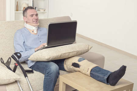 neck brace: Man with leg in neck brace, knee cages and crutches for stabilization and support resting on a sofa with laptop.