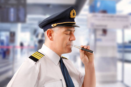 Airline pilot wearing uniform with epaulettes smoking electronic cigarette. photo