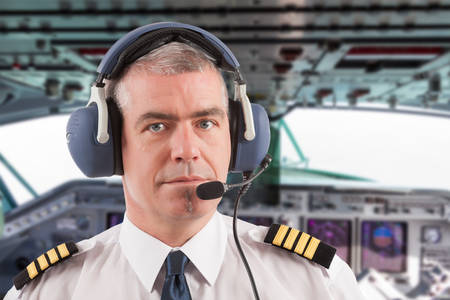 Airline pilot wearing uniform with epaulettes and headset, on board passenger aircraft. Stock Photo
