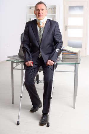accidente trabajo: Hombre de negocios en el trabajo que lleva cuello ortopédico con muletas