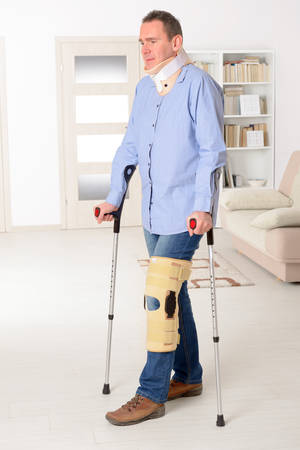 stabilization: Man with leg in neck brace, knee cages and crutches for stabilization and support
