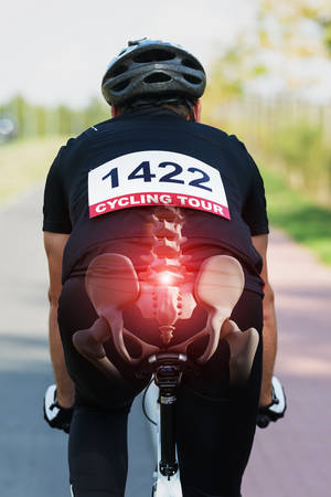 Cyclist riding a bike with digital composed hip bones and spine Standard-Bild