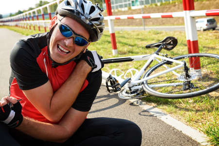 shoulder problem: Bicycle accident. Biker holding his shoulder. Stock Photo