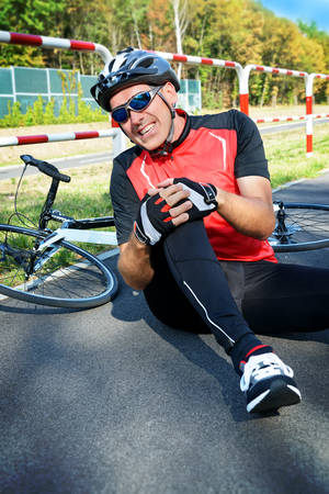 cycling: Bicycle accident. Biker holding his knee.