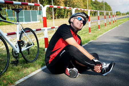 sport bike: Bicycle accident. Biker holding his ankle.