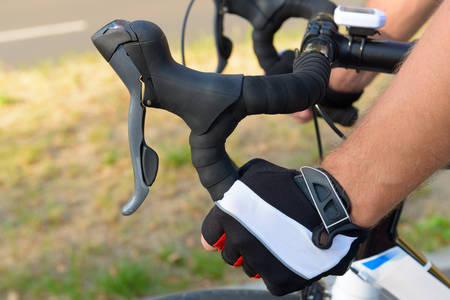 handlebars: Hands in gloves on bicycles handlebars