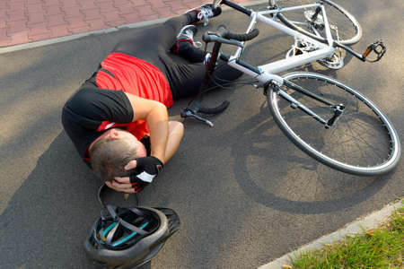 holding the head: Bicycle accident. Biker lying on the road and holding his head