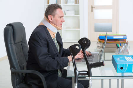 recovering: Businessman at work wearing neck brace with crutches Stock Photo