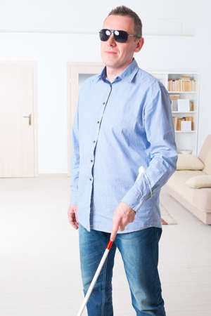 blind person: Blind man with white stick and dark glasses at home