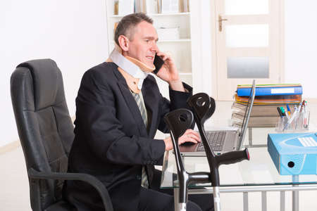 disability insurance: Businessman at work wearing neck brace with crutches Stock Photo