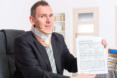 neck brace: Businessman at work wearing a neck brace with insurance claim form in hands Stock Photo