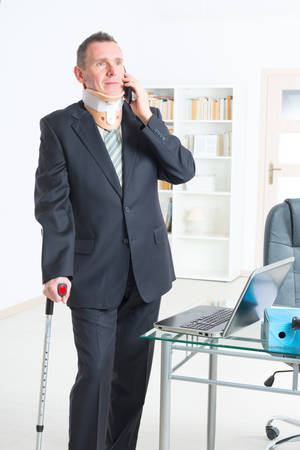 neck brace: Businessman at work wearing neck brace with crutches Stock Photo