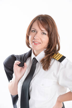 aircrew: Beautiful woman pilot wearing uniform with epauletes, standing isolated on white background. Stock Photo