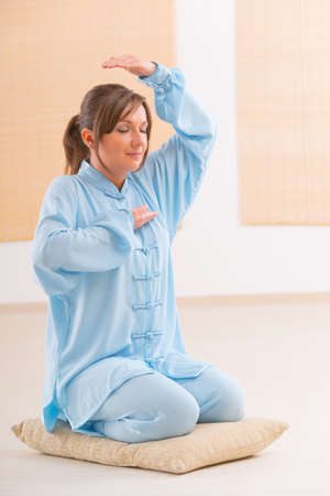 qigong: Beautiful woman doing qi gong tai chi exercise wearing professional, original Chinese clothes at gym